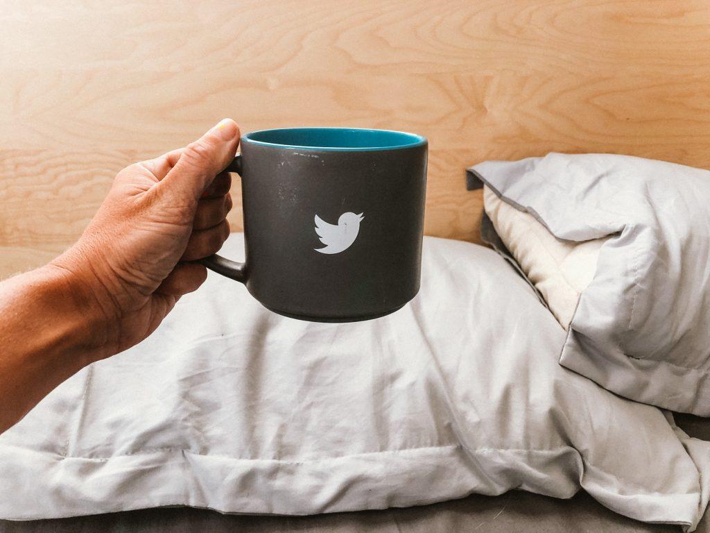Hand holding mug with a tweeter bird sign