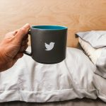 Hand holding mug with a tweeter bird sign