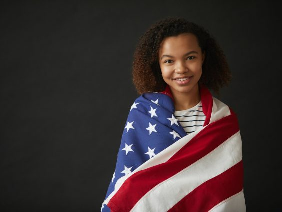 Young African Woman Holding American flag on Black